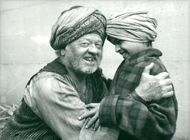 """Mickey Rooney as the magician Daad-el-Shur with one of the children's actors during the filming of the movie """"Arabian Adventure"""" at Pinewood"""