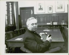 Harold Wilson siting while holding a pipe in the meeting.