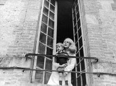 Catherine Deneuve on balcony with a child.