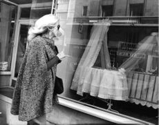 Catherine Deneuve looking at shopping windows.