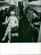Men and women siting in the airplane and talking together going to a trip, 1967.