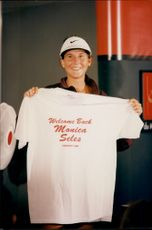 """The tennis player Monica Seles holds up the t-shirt with the text """"Welcome Back Monica Seles"""" during the Canadian Open 1995"""