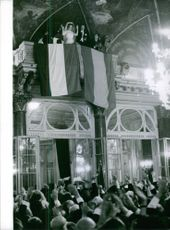 Carlos Hugo and his wife Princess Irene raise their hands in front of the cheering crowd, 1964.