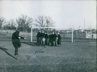 A footballer kicked football while others standing in front of net to stop it before goal during training.1944