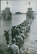Camouflaged American jungle fighters form a line to pass ammunition through the South Pacific surf from a landing craft to Rendova Island in the Central Solomons. The landing on Rendova provided an Allied base for the campaign that freed New Georgia Islan