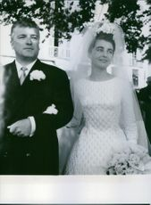 Marina Gacry holding the arm of the man beside her on her wedding day. 1960.