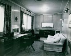 """the Duke's private room. Complete panelling in natural wood. Grey carpets, bright grey desk. Blue chairs, Beige sette cover. In glass case sclae model of the Duke's ship """"Magpie""""."""