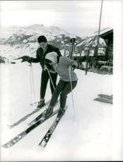 Sacha Distel enjoying skiing with woman.