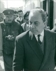Fazıl Küçük with Major Edward Macey surrounded with people while walking on the street.