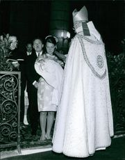 Marie Françoise standing in the church for christening her baby.
