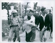 A child being led by soldier forcefully.