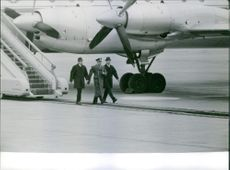 Officers and pilot are walking on a ramp. 1961