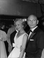 Yul Brynner standing with his wife.