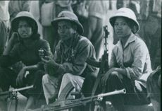 Women and man soldiers sitting and holding gun. 1968