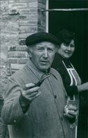 Photograph of a man with a smoking pipe in his hand and a woman, standing just behind him.