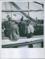 1945 Men siting in the boat and talking to each other.
