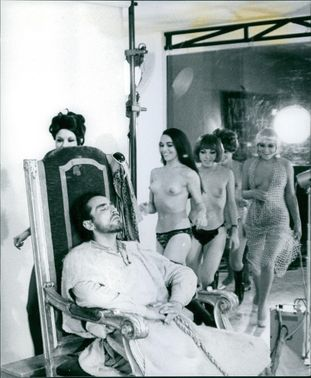 Vittorio Gassman relaxing, naked women looking at him and smiling.