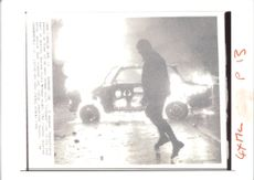 A trabant car blazes behind one of the masked extremists who fought police with molotov.