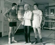 Two men and a woman standing with boxing bag.