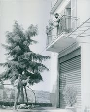 Woman standing in balcony and talking to a man standing beneath her building.