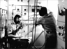 Two men in control room.