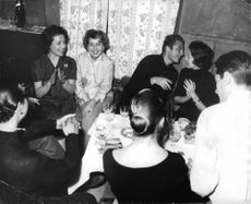 Soraya Esfandiary Bakhtiari in a gathering with freinds of her age, sitting with a man ready to kiss him.