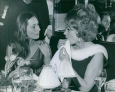 Lila Kedrova  talking to a woman while having their meal. 1965