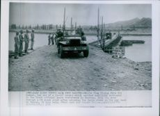 White flag flying on its bumper, one car moving with some soldiers in Korea.