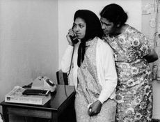 A woman speaking on a telephone while the other one standing behind trying to listen.