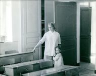 A woman standing with a child in the classroom.