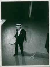 Maurice Chevalier standing.