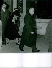Maurice Challe walking out of a building with other people following him. 1961