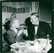 Maurice Chevalier sitting with woman and toasting.