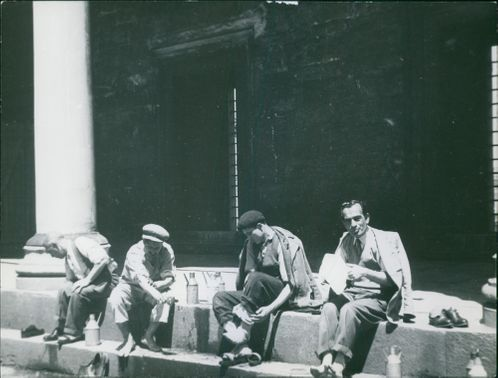 Men having a meal on along the street side.
