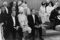 Begum Om and Aga Khan IV sitting together with other people.  - Oct 1967