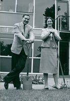 Audrey Elizabeth Callaghan and Leonard James Callaghan holding planting tools. 1976.