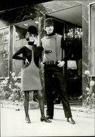 Man and woman models wearing their subject clothing and hats along the pathway in 1966