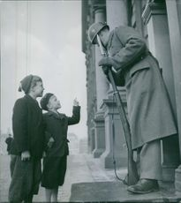 Two kids talking to a soldier, 1944.