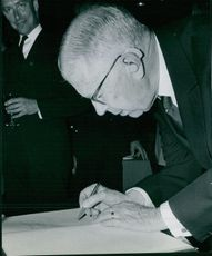 Photo of a man signing a  paper.