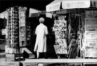 Woman at a kiosk with postcards and newspaper stand