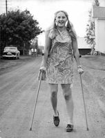An injured young lady, standing and smiling, holding a cane on both hands while striking a pose.
