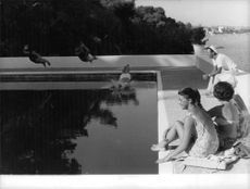 Aga Khan IV sitting on boundary of swimming pool.