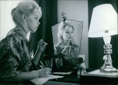 Jill Haworth sitting behind a desk while writing on a piece of paper.
