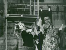 Woman and a man singing and dancing on stage.  - May 1969