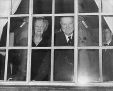 Winston Churchill with his wife peeping through window.