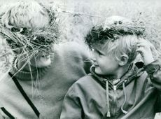 Mother and her child wearing crowns made of twigs over their head.