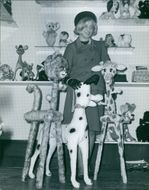 Woman standing in a toy shop, looking towards the camera and smiling, 1964.