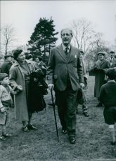 Young boy looking at Maurice Harold Macmillan.  Holding his mother's hand tightly a young boy gazes intently at the British Premier.