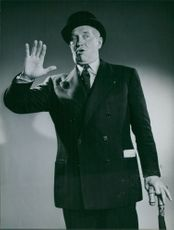 Maurice Auguste Chevalier standing.