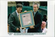 Eric Heiden handed a plaque to John McEnroe at a ceremony in connection with John McEnroe's enrollment at the International Tennis Hall of Fame